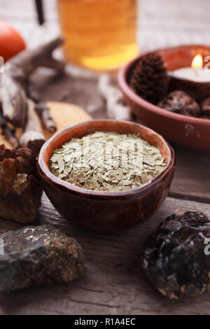 Healthy tea, dry herbs, plants, candle and stones on wooden table. Homeopathy and herbal alternative medicine. - Stock Photo