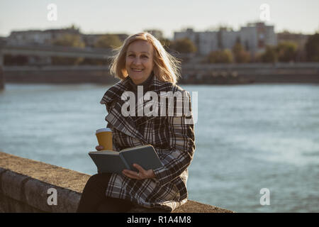 Senior woman enjoys reading book and drinking coffee while sitting by the river. - Stock Photo