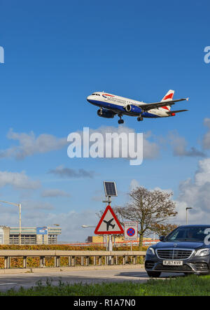 LONDON, ENGLAND - NOVEMBER 2018: Road sign on the A30 road at London Heathrow Airport warning motorists of low flying aircarft. In the background is a - Stock Photo