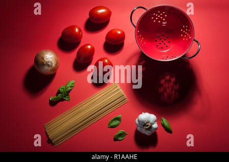 Seeing red - making pasta sauce. A deconstructed scene showing the ingredients used to make pasta and sauce. - Stock Photo