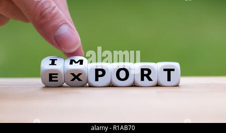 Hand is turning a dice and changes the word 'import' to 'export' - Stock Photo