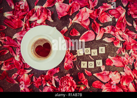 Flat lay cup of coffee with heart shape pattern and message I love you spelled in wooden blocks with red peony flower petals on black background. Vale - Stock Photo