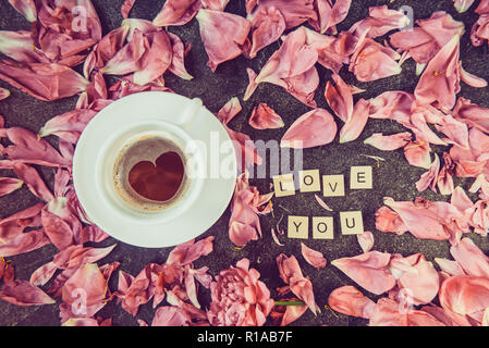 Flatlay cup of coffee with heart shape pattern and message I love you spelled in wooden blocks with pink peony flower petals on dark background. Valen - Stock Photo