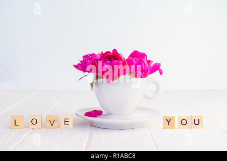 Close up purple pink peony flowers bouquet in a decorative cup and saucer and message I love you spelled in wooden blocks on white wooden background.  - Stock Photo