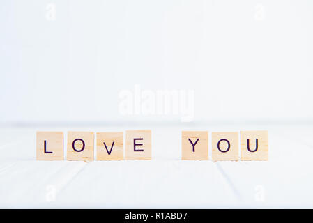 Message I love you spelled in wooden blocks standing on white wooden table. Valentines day background. Simplicity concept. Selective focus. Copy space - Stock Photo