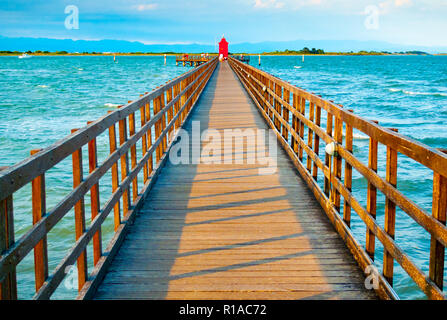 Wooden pier leading to a red lighthouse at sunset in Lignano Sabbiadoro, Friuli, Italy Stock Photo