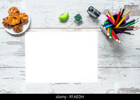 Colored multicolored pencils in a cup, a sheet of white paper isolated, old style clock, plate with cake on a vintage wooden background, wooden worn b - Stock Photo