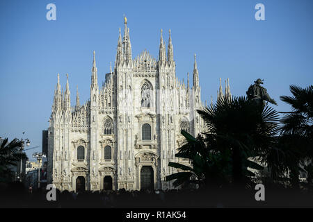 The Duomo Cathedral in Milan, Italy with the newly planted palm trees and the equestrian statue of Vittorio Emanuele II - Stock Photo