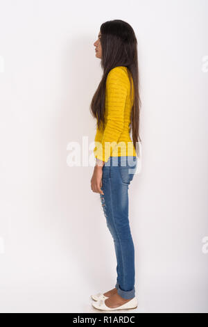 Full body shot profile view of young Indian woman standing again - Stock Photo