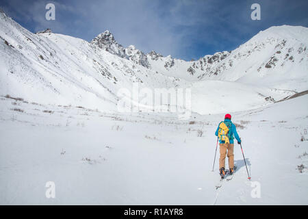 A skier walks in the mountains - Stock Photo