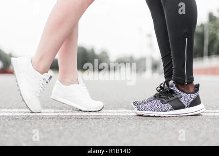 Love sport concept - running couple kissing. Closeup of running shoes and girl standing on toes to kiss boyfriend during jogging workout training outd - Stock Photo