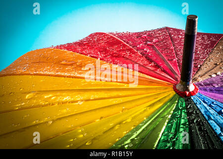 Multi-colored colorful umbrella with all colors of the rainbow with raindrops. - Stock Photo