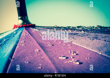 Raindrops on a colorful umbrella with all the colors of the rainbow close-up macro waterdrops background. Vintage, grunge, old, retro style photo. - Stock Photo