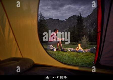 View from inside tourist tent at sunset. Alone tourist, man hiker sitting at bonfire - Stock Photo