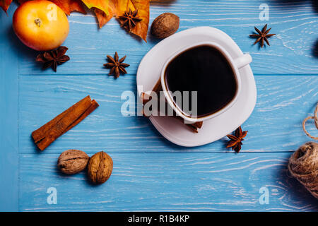 Black coffee in a white cup on a saucer with cinnamon walnut anise and apple on a blue surface - Stock Photo