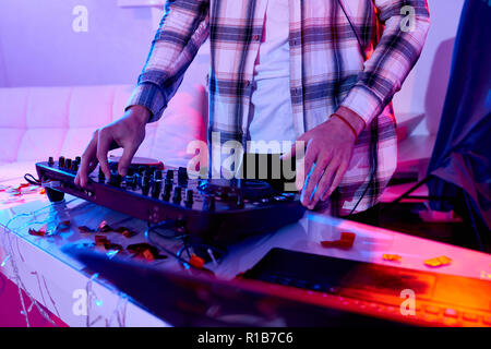 Faceless shot of man in shirt mixing music on DJ console at table in bright lights having party for New Year celebration - Stock Photo