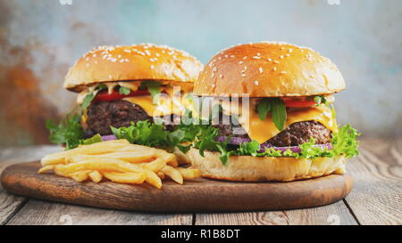 Two fresh homemade burgers with fried potatoes on a wooden table - Stock Photo