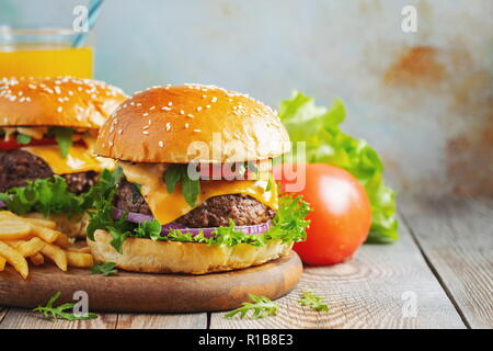 Two fresh homemade burgers with fried potatoes and orange juice on a wooden table. With copy space - Stock Photo