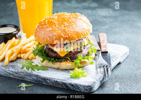 Two fresh homemade burgers with fried potatoes on a stone table - Stock Photo