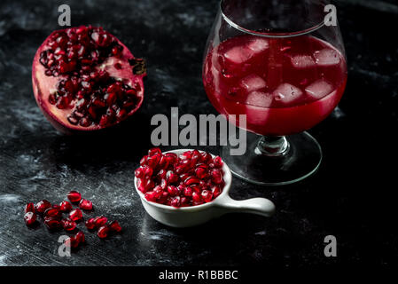 Tempting pomegranate, red seeds and fresh juice with the addition of ice on a black, stone background - Stock Photo