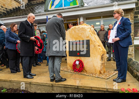 Yeadon, Leeds, West Yorkshire, UK 11th November, 2018. People are gathered round the new war memorial stone in front of Yeadon Methodist Church for a service of dedication & remembrance. The first poppy wreath has been laid and a man is bowing his head in respect. Ian Lamond/Alamy Live News. - Stock Photo