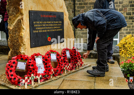 Yeadon, Leeds, West Yorkshire, UK 11th November, 2018. Close-up of the plaque inscription & crosses & poppy wreaths laid at the base of the new war memorial stone in front of Yeadon Methodist Church, on the anniversary of the end of the First World War. A man is bending down placing a cross in the ground. Ian Lamond/Alamy Live News. - Stock Photo