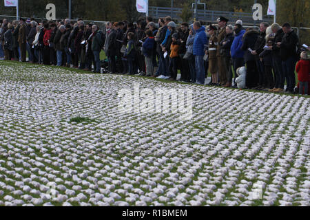 Queen Elizabeth Olympic Park, Stratford, London - 11 November  2018: People seen during the remembrance day memorial service at Elizabeth Olympic Park, London around 72,396 shrouded figures created by artist Rob Heard in memory of the fallen Commonwealth soldiers at Somme who have no known grave. The installation is made up of hand-sewing calico shrouds and bound over small figures by artist Rob Heard. Credit: David Mbiyu /Alamy Live News - Stock Photo