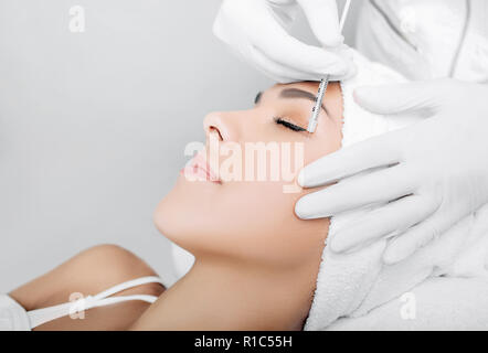 Beautiful woman having facial injection into area near eye. Anti age collagen injections into face. Beautician making injections against wrinkles arou - Stock Photo
