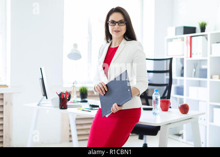 A young girl standing near the table in the office and holding a Board with sheets. - Stock Photo
