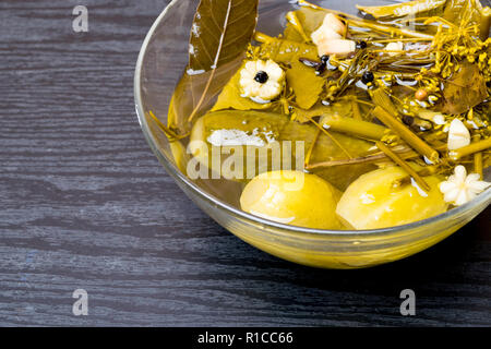 Homemade marinated cucumbers with dill, garlic, bay leaf, pepper and spices in a glass bowl, selective focus - Stock Photo