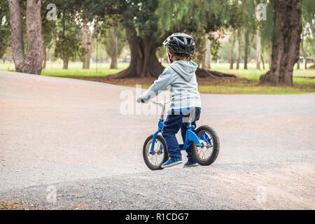 Australian kid riding his balance bike in the park, South Australia - Stock Photo