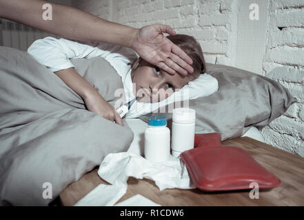 Sweet sick cute girl feeling sick with high fever lying in bed with medicines thermometer hot water bag suffering from Cold and Winter Flu Virus and G - Stock Photo