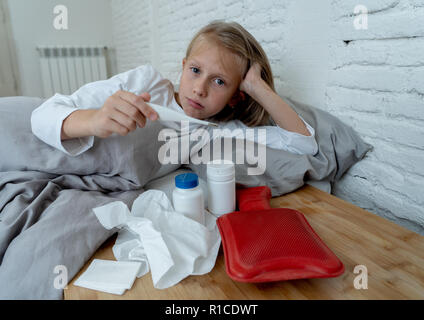 Sweet sick cute girl feeling sick lying in bed with medicines thermometer hot water bag suffering from Cold and Winter Flu Virus Sneezing Running Nose - Stock Photo