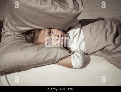 Unhappy girl covering her ears with pillow trying to sleep at night feeling sleepless sad and tired in Parents arguing Family fights Children Sleeping - Stock Photo