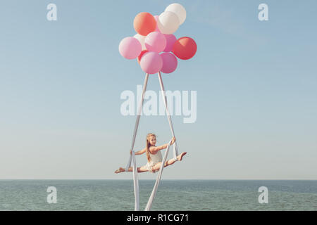 Little girl acrobat makes the twine on the canvases. - Stock Photo