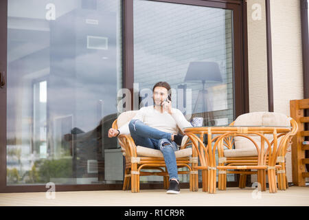 Male sitting on outdoors armchair and talking by phone - Stock Photo