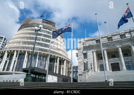 Flags flutter in front New Zealand Government buildings, House neo classical style House of Parliament with Beehive behind. - Stock Photo