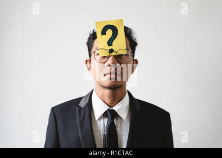 Young Asian businessman with QUESTION MARK on his forehead. Concept of business solution, planning and problems - Stock Photo