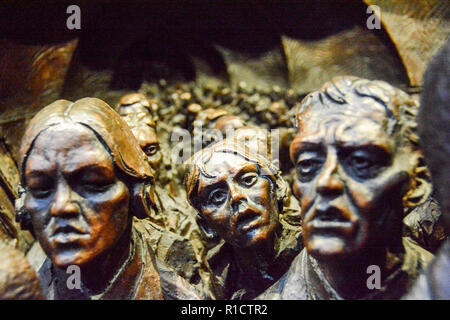 Reliefs around the plinth of Paul Day's The Meeting Place sculpture at St Pancras station, London, UK - Stock Photo