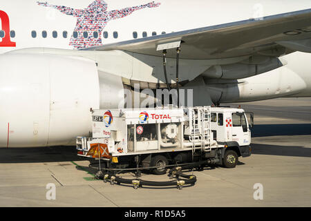 A Total aviation fuel truck refuelling an Austrian Airlines passenger airliner at Vienna Airport - Stock Photo