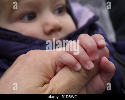 Baby hand gripping an adult hand by the thumb with out-of-focus face in the background - Stock Photo