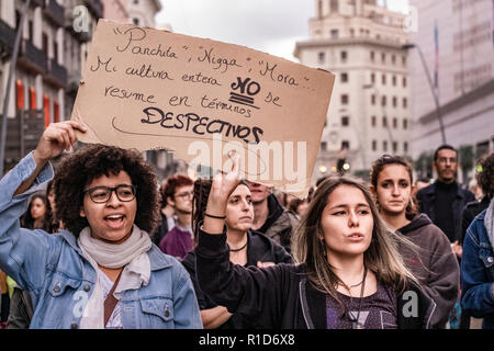 Two young women are seen holding a placard against institutional racism during the protest.  A new manifestation against institutional racism has crossed the streets of the center of Barcelona. Accompanied by social organizations and the Trade Union of street vendors, more than 500 people have claimed to end racism in Barcelona and have denounced police identifications according to the color of their skin. - Stock Photo