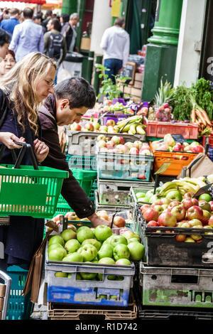 London England United Kingdom Great Britain South Bank Southwark Borough Market vendors stalls produce fruits vegetables apple crates woman man shoppi - Stock Photo