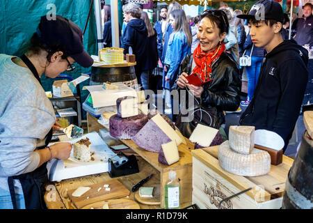 London England United Kingdom Great Britain South Bank Southwark Borough Market vendors stalls cheesemonger imported cheese artisanal shopping Asian w - Stock Photo