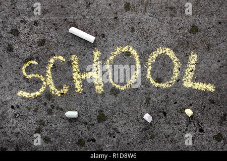 Colorful chalk drawing on asphalt: Yellow word SCHOOL - Stock Photo