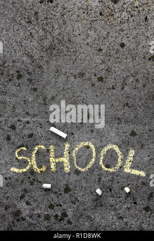 Colorful chalk drawing on asphalt: Yellow word SCHOOL. Copy space - Stock Photo