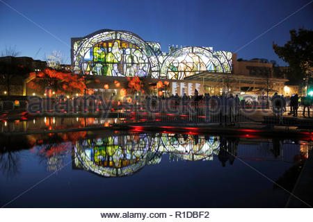 Edinburgh, United Kingdom. 11th November, 2018.  The Scottish Parliament building illuminated on Armistice day with images that tell the story of the world war 1 conflict alongside a Roll of Honour of those who died, reflected in the ornamental pond.   Credit: Craig Brown/Alamy Live News. - Stock Photo