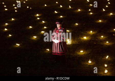 London, UK. 11th November 2018. Beefeater standing in the Tower of London moat. Beyond the Deepening Shadow is an installation where 10000 flames are lit for Rememberance Sunday. Credit: Dimple Patel/Alamy Live News - Stock Photo