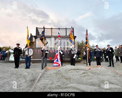 West Wittering Beach Commemorates Armistice Day -The Wittering Royal British Legion  take the salut when West Wittering Estate invited local residents and visitors to join them on Wittering beach to commemorate 100 years since the end of WWI. Inspired by Danny Boyle's 'Pages in the Sea' Ð a national art event  Location in front of local sculptor Alexandra Beale's  silhouette in the sand of Charles Henry Kewell, one of four brothers from the West Wittering Kewell family killed in the war.Contributor: Gary Blake / West Wittering Estate /Alamy Stock Photo - Stock Photo