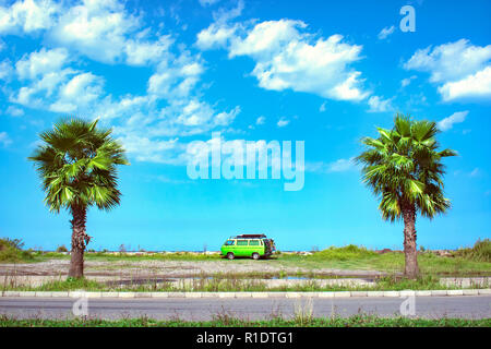Fully equipped old timer camper van parked on the beautiful long beach between two palm trees on a bright sunny summer day - Stock Photo